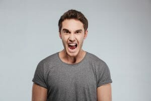 Portrait of a young angry man screaming and looking at camera over white background