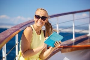 Young smiling woman in sunglasses holding tablet computer and looking somewhere while taking time off traveling by ship