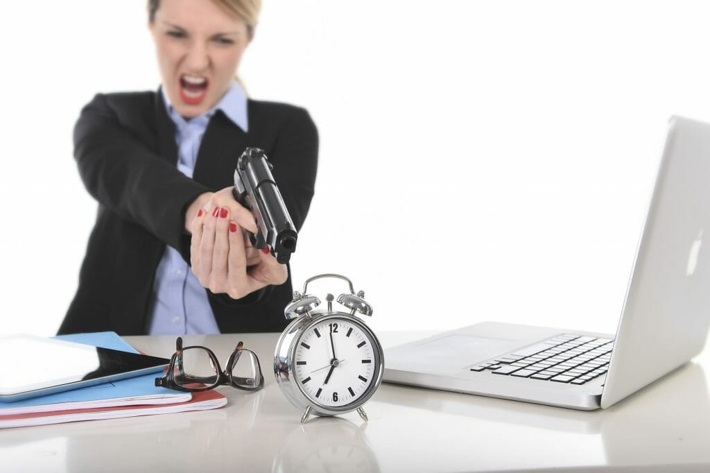 young attractive businesswoman furious and angry working with computer laptop pointing gun to alarm clock in out of time, long hours of work and project deadline stress