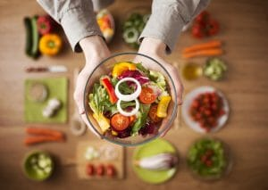 Hands holding an healthy fresh vegetarian salad in a bowl, fresh raw vegetables on background, top view