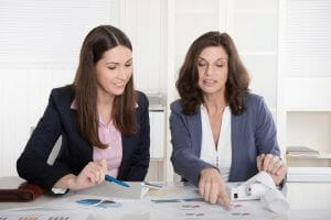 Two business woman analyzing balance sheet, customer trust