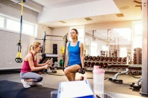 morning routine in gym, woman with personal trainer exercising